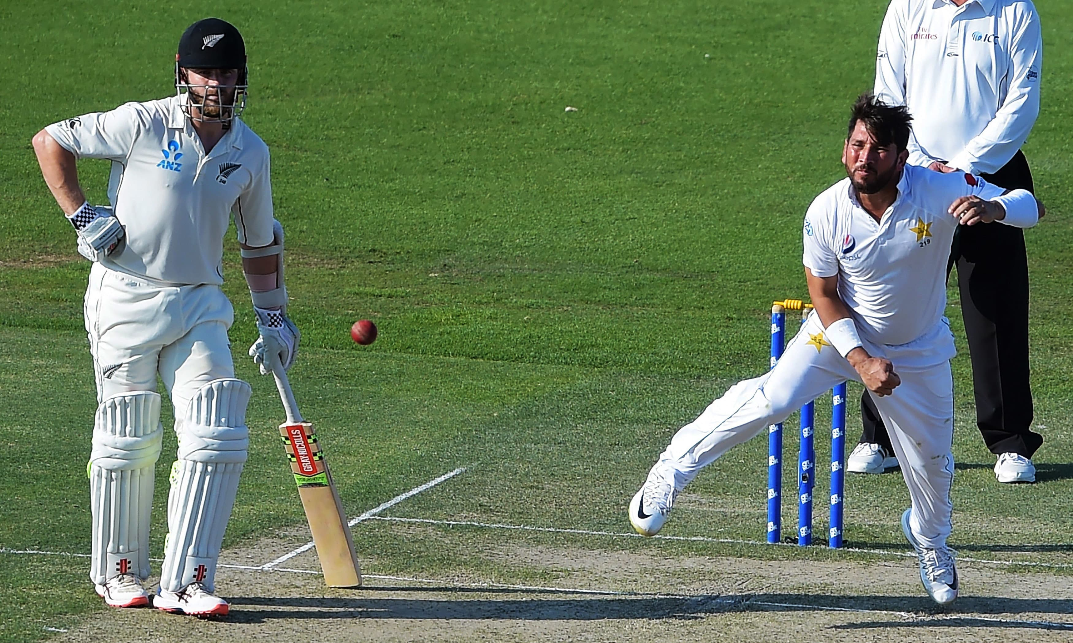 Yasir Shah delivers the ball as Kane Williamson looks on during the first day of the third Test. —AFP