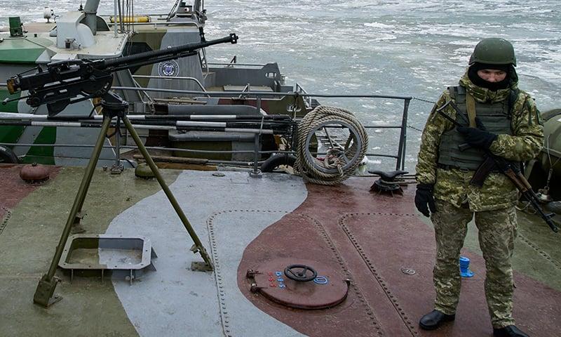 A Ukrainian serviceman stands on board a coast guard ship in the Sea of Azov port of Mariupol, eastern Ukraine on Monday. — AP