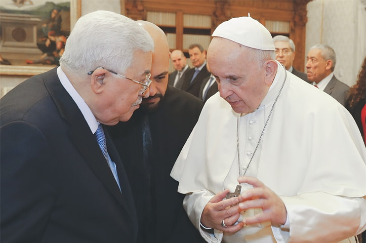 Pope Francis talks to Palestinian President Mahmoud Abbas as they exchange gifts during a private audience at the Vatican on Monday.—AP