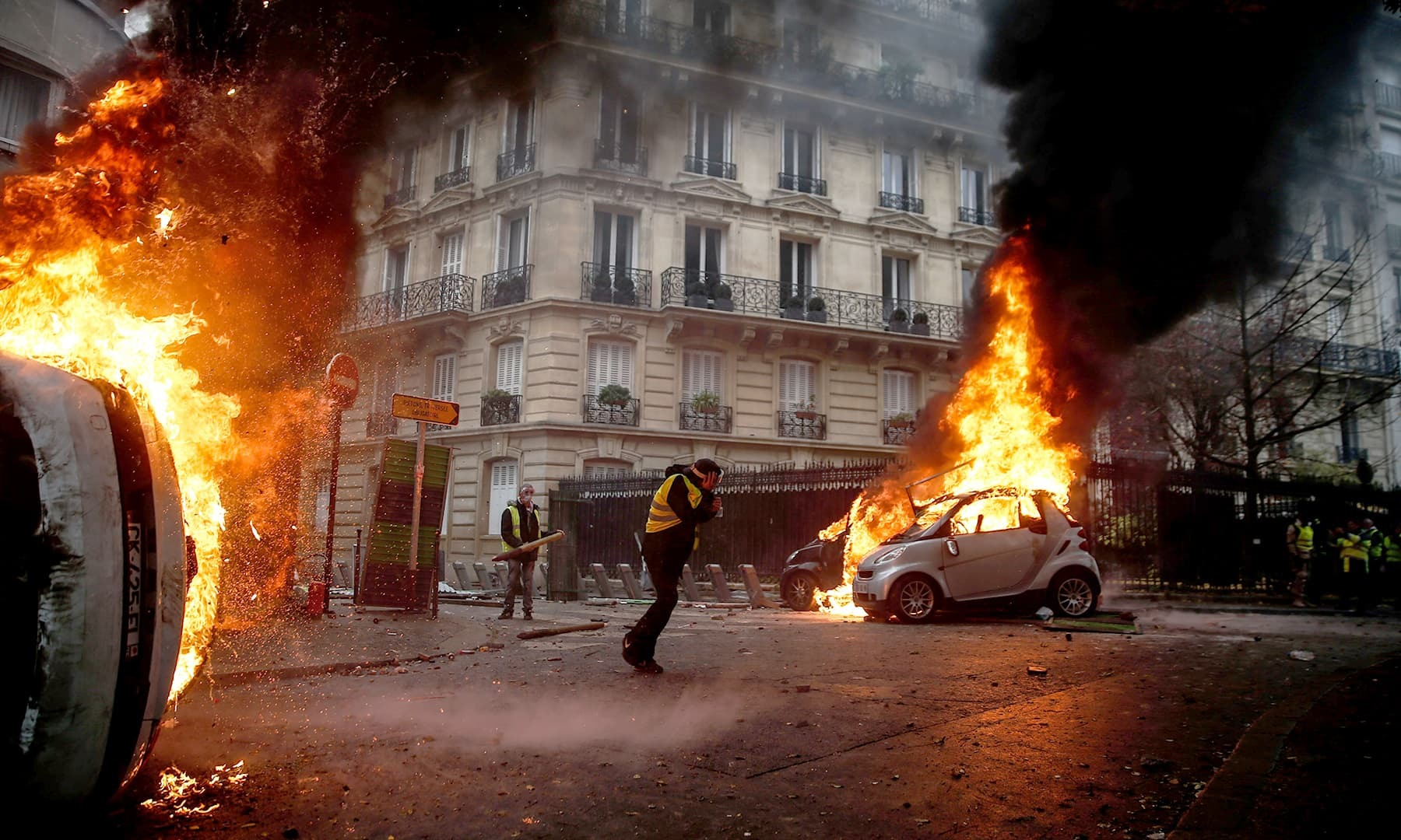 Protesters walk by burning cars during clashes with riot police on the sideline of a protest of Yellow vests (Gilets jaunes) against rising oil prices and living costs. — AFP