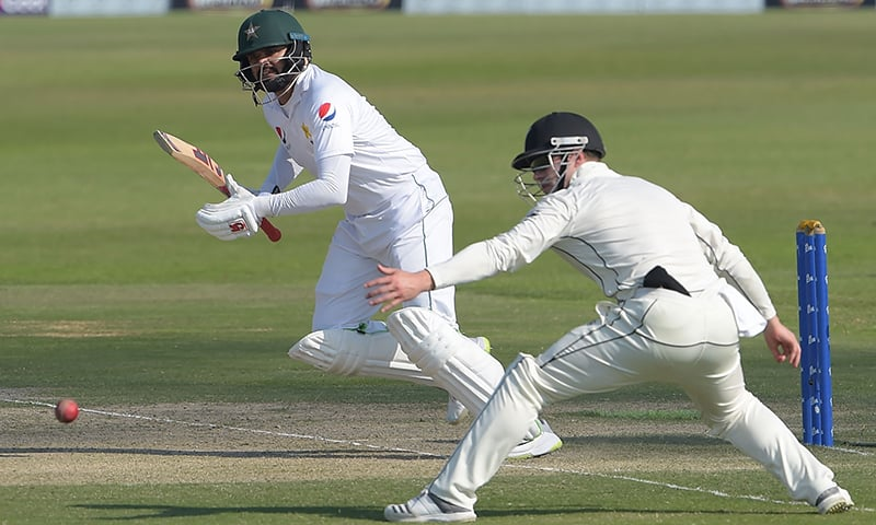 Azhar Ali (L) plays a shot as New Zealand cricketer Henry Nicholls looks on. — AFP