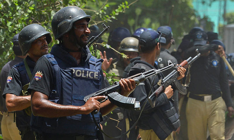 Policemen look on with their weapons during clashes with supporters of Tahirul Qadri in Model Town, Lahore on June 17, 2014. —AFP/File