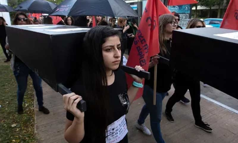 اسرائیلی لڑکیاں ہلاک ہونے والی خواتین کے علامتی تابوت اٹھائے احتجاج کررہی ہیں — بشکریہ دی گارجین