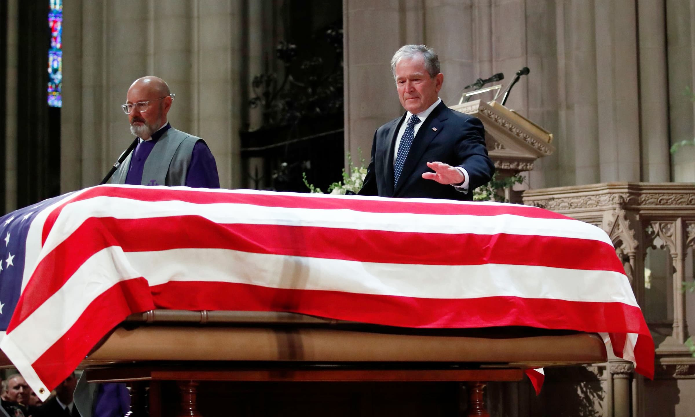 Former US President George W Bush leaves after speaking at the State Funeral for his father. —AFP