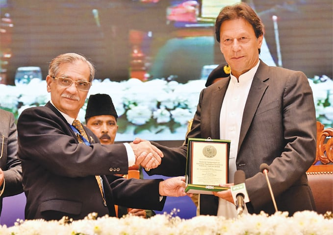 CHIEF Justice of Pakistan Mian Saqib Nisar presenting an appreciation shield to Prime Minister Imran Khan on Wednesday.—APP