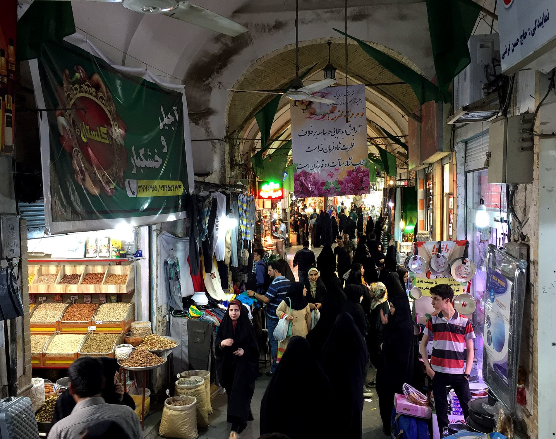 Shoppers inside Qom's historic bazaar, where pilgrims search for souvenirs, devotional icons, and local sweets famous to the city.