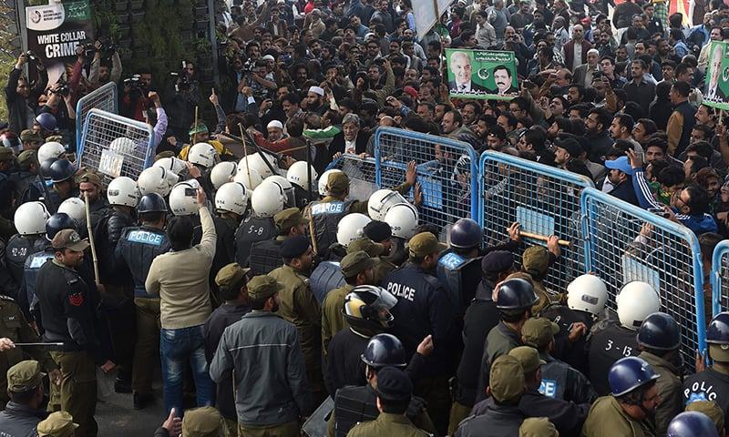 Policemen hold PML-N supporters outside the accountability court. — AFP