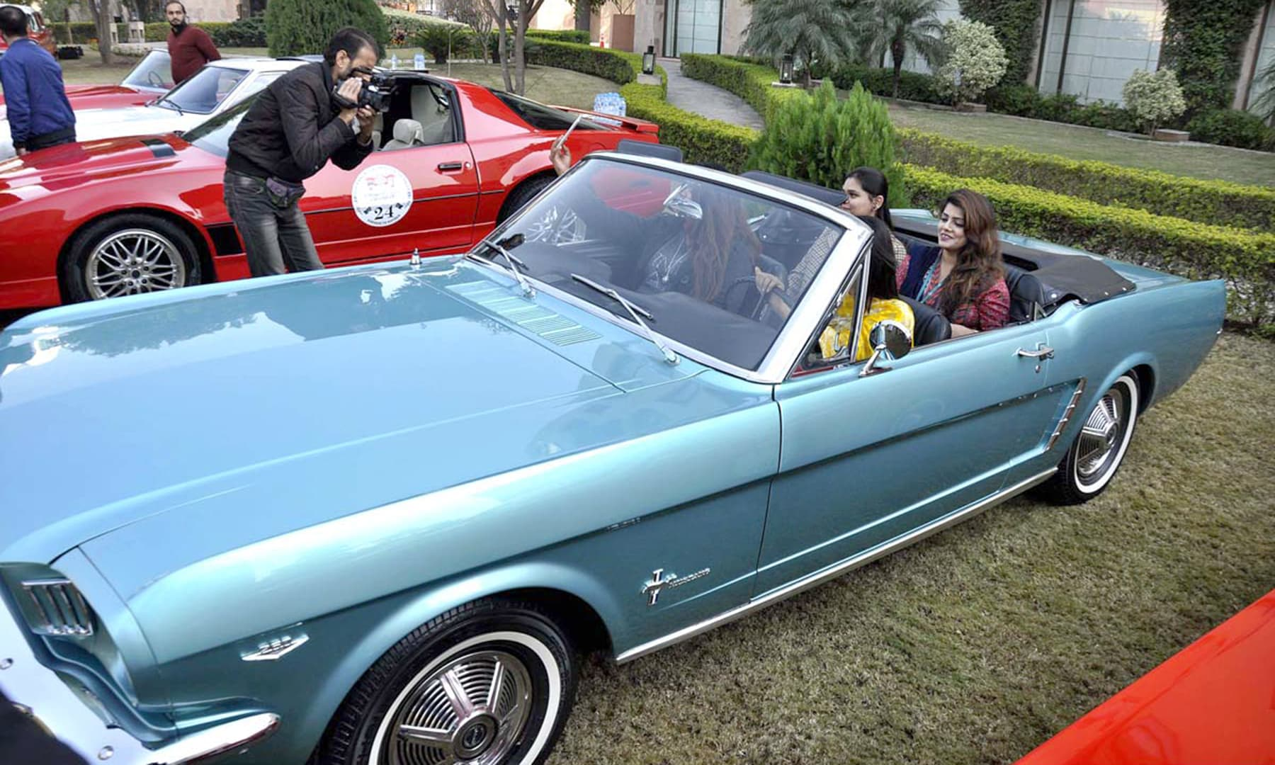 "Visitors posing inside a classic vehicle at the ""Heritage on wheels"" event in Islamabad. —APP"