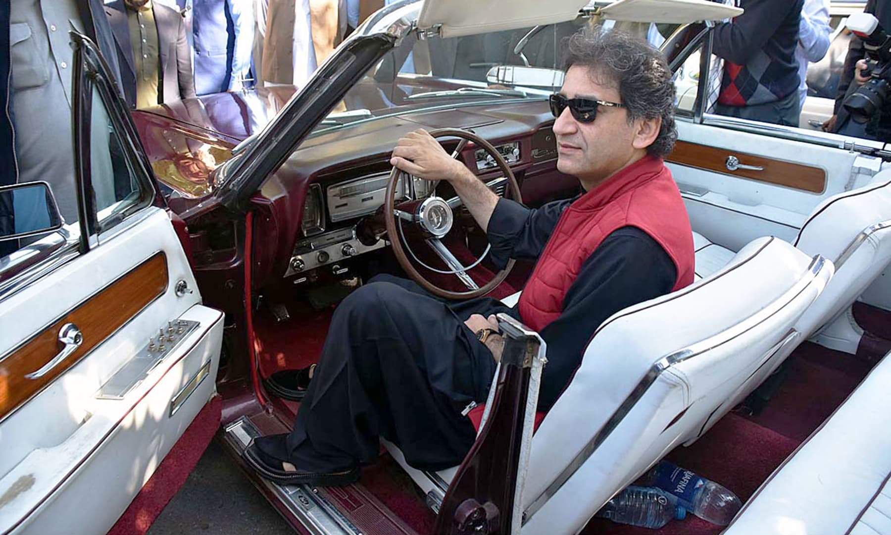 Senior Minister of Tourism, Sports, and Culture Mohammad Atif Khan interacting with the displayed vehicles at the classic car show in Peshawar. —@PTIofficial