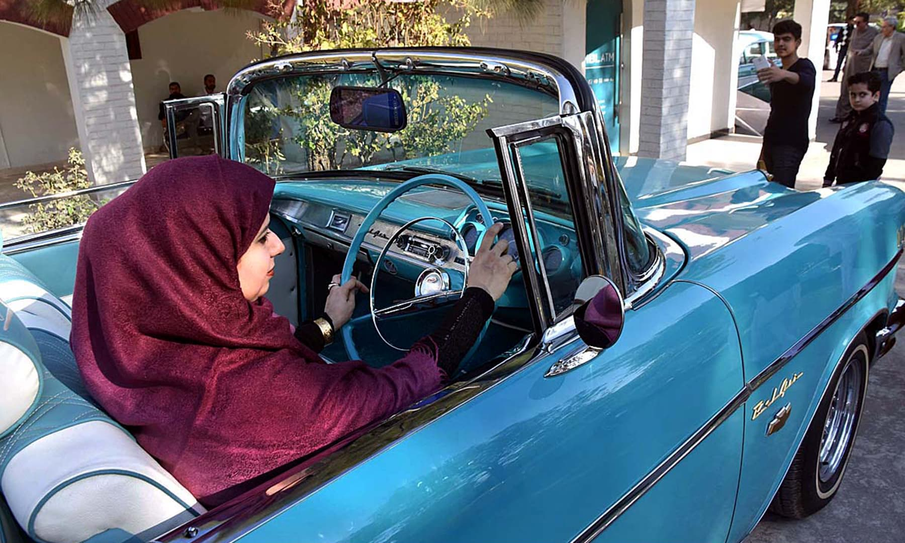 A woman gets behind the wheel and looks in the side view mirror of a classic car displayed in Peshawar. —@PTIofficial