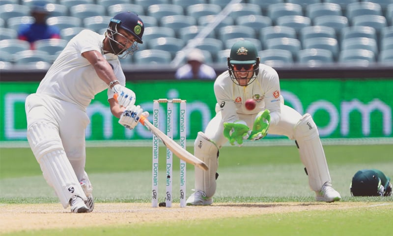 ADELAIDE: Australian captain Tim Paine watches as India's Rishabh Pant scoops a catch during the first Test at the Adelaide Oval on Sunday.—AP