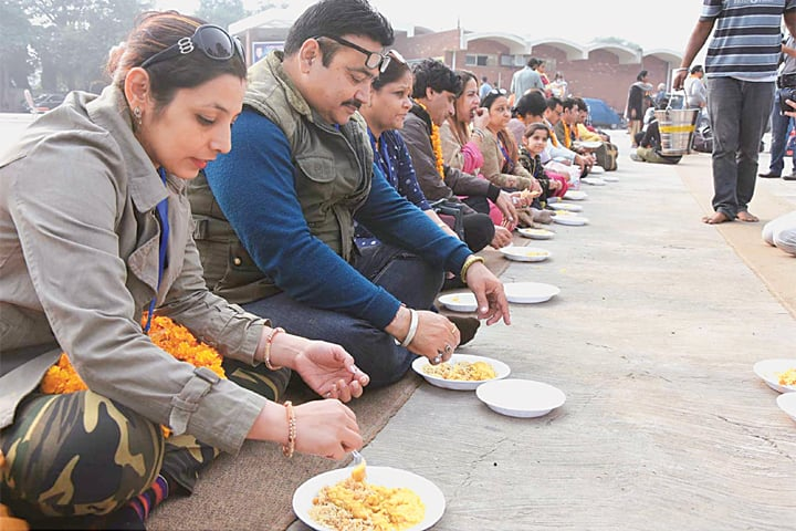 LAHORE: Hindu pilgrims enjoy food after crossing the Wagah border on Sunday.—APP