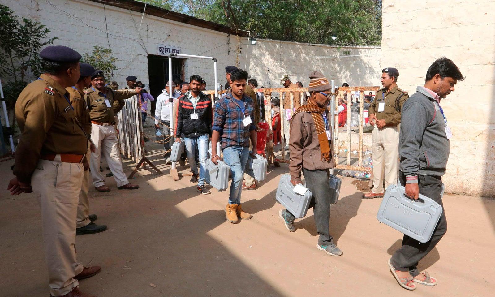 الیکشن ورکرز انتخابات سے قبل الیکٹرانک ووٹنگ مشین لے کر جارہے ہیں — فوٹو : اے ایف پی