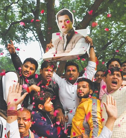 CONGRESS supporters hold a bust placard of Rahul Gandhi as they celebrate the party's poll victories on Tuesday.—AFP