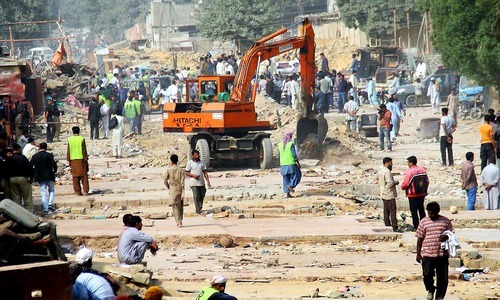 Karachi Metropolitan Corporation workers use heavy machinery to demolish encroachments during an anti-encroachment operation at the Gharibabad furniture market along the Karachi Circular Railway. ─ Online