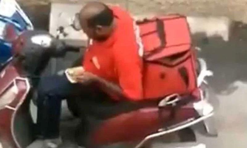 ویڈیو میں ڈیلیوری مین مزے سے کھانے کھاتے ہوئے نظر آتا ہے—اسکرین شاٹ