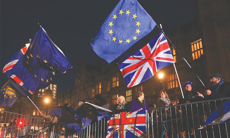 ANTI-BREXIT campaigners wave Union and EU flags outside the Houses of Parliament in London on Wednesday.—AFP