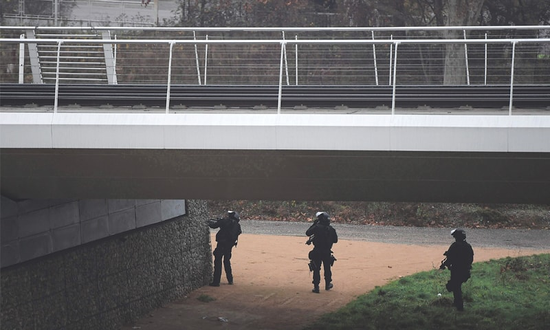 STRASBOURG: Security personnel carry out a search operation on a bank of the river Rhine on Wednesday.—AFP