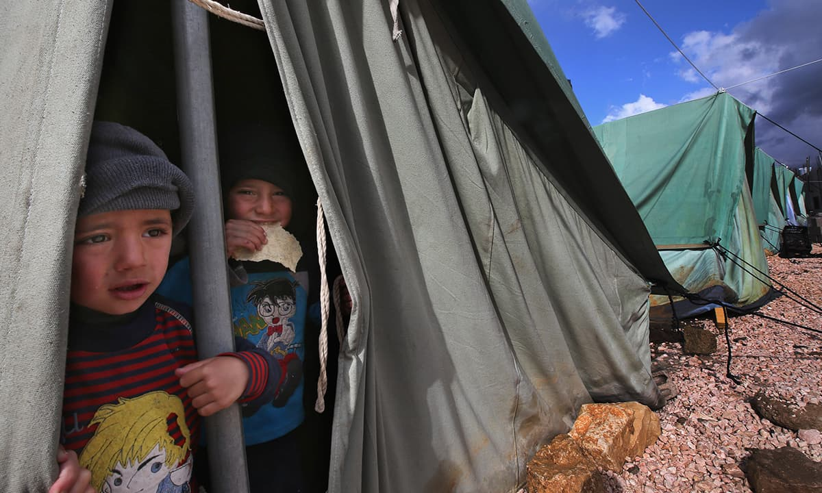 Syrian refugee boys look outside their tent at a temporary refugee camp in the eastern Lebanese town of Marj | Associated Press