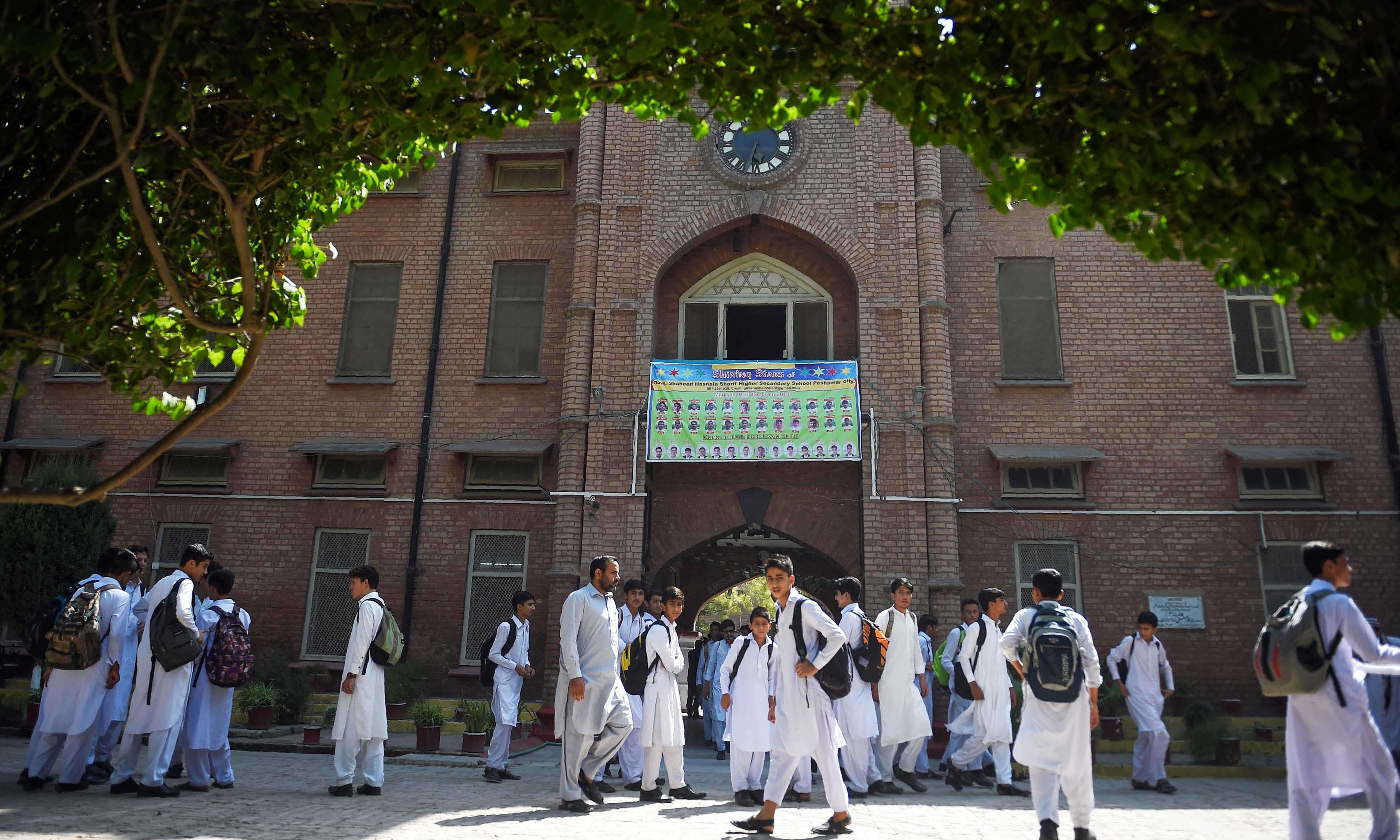 Children gather outside a school in Peshawar. —AFP