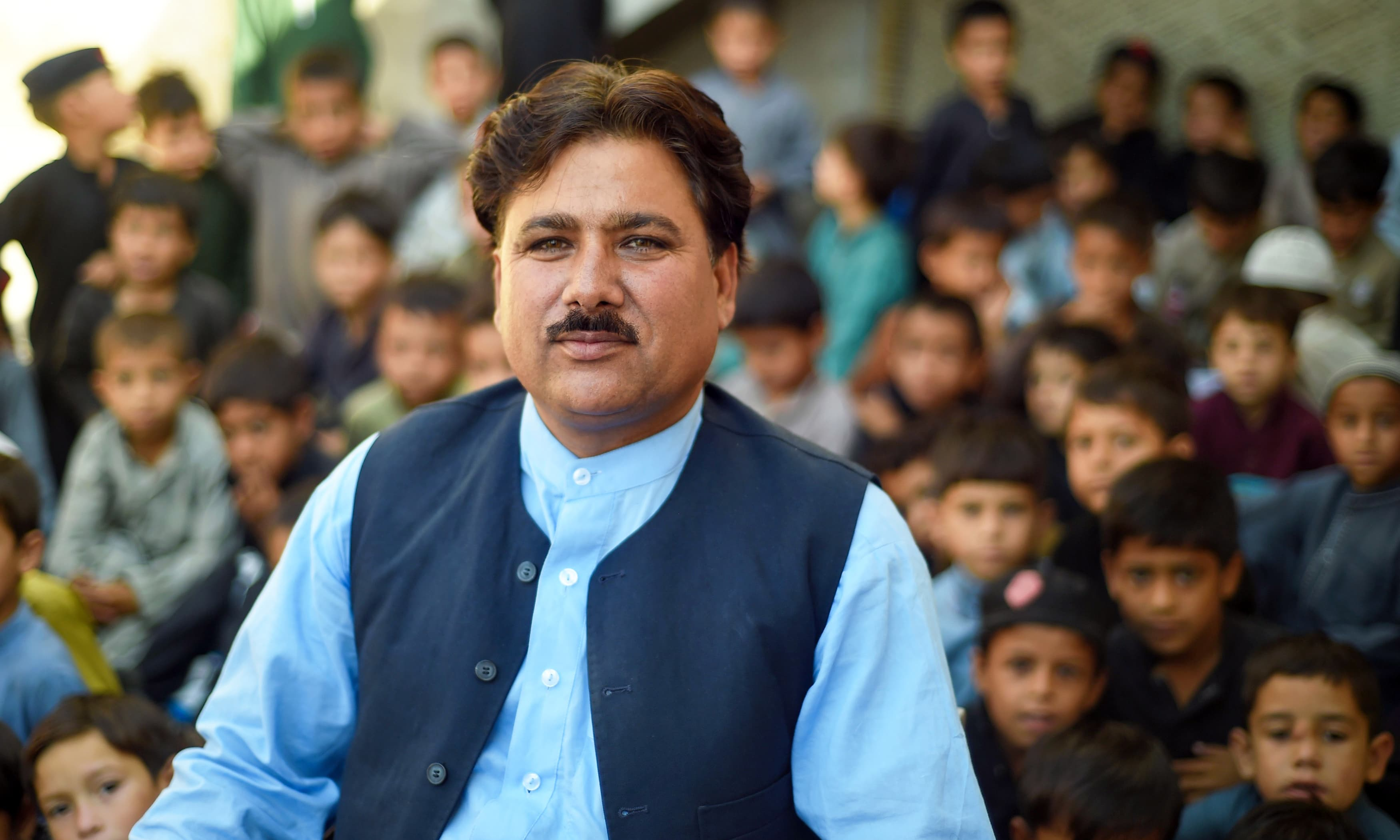 Faisal Khaliq, a director at the education department, poses with children outside a school in Mingora. —AFP