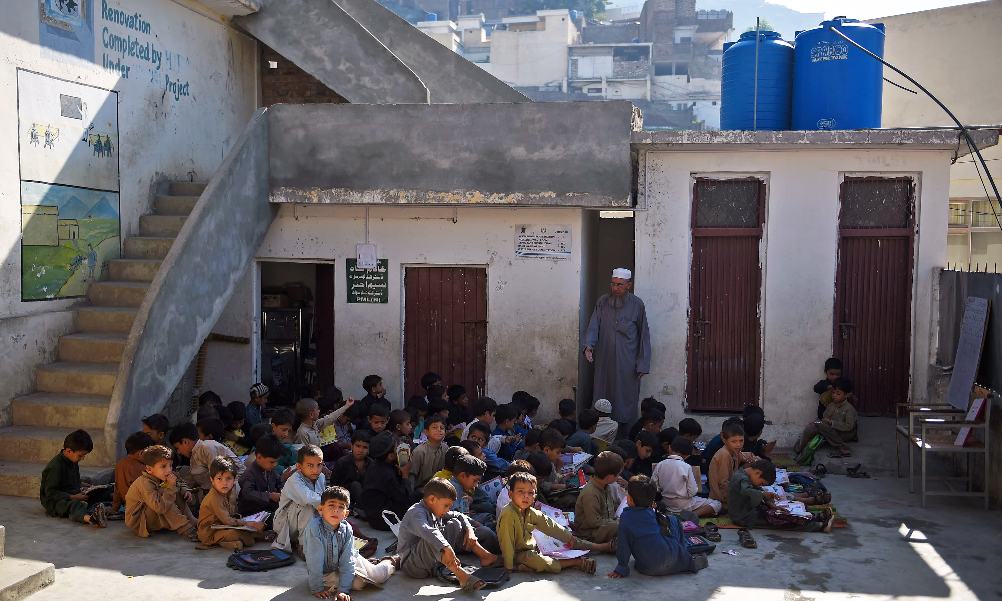 Boys attend a class outside a school in Mingora, a town in Swat Valley. —AFP