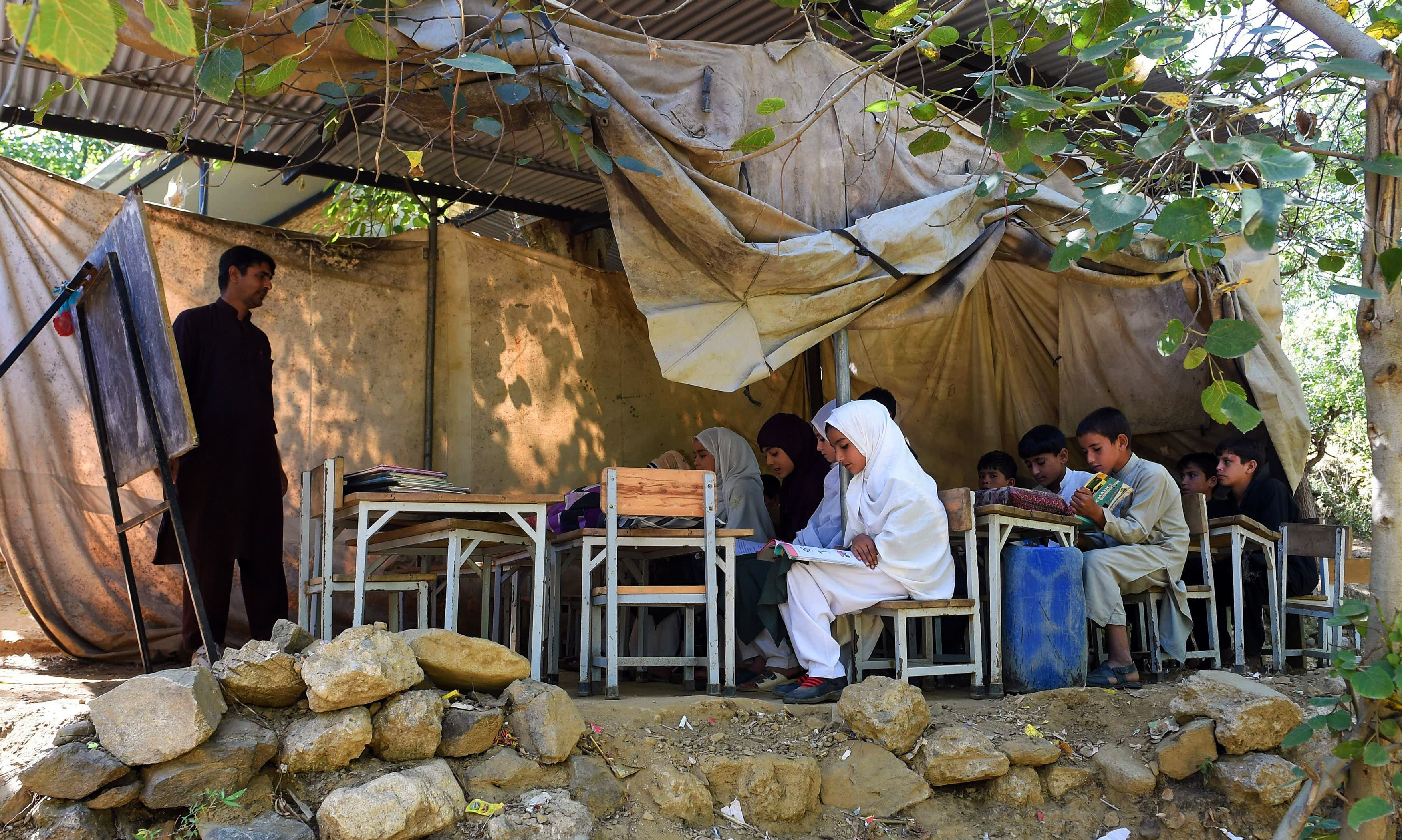 In this picture taken on September 18, 2018, children attend a class at a tent school in Tanjai Cheena, a village in Swat Valley. - At the Tanjai Cheena school in northwest Pakistan students squeeze into makeshift classrooms where plastic tarps serve as walls and electricity is sparse, as a surging population overstretches the country's fragile education system. (Photo by FAROOQ NAEEM / AFP) / TO GO WITH Pakistan-education-demographics,FOCUS by Joris FIORITI — AFP or licensors