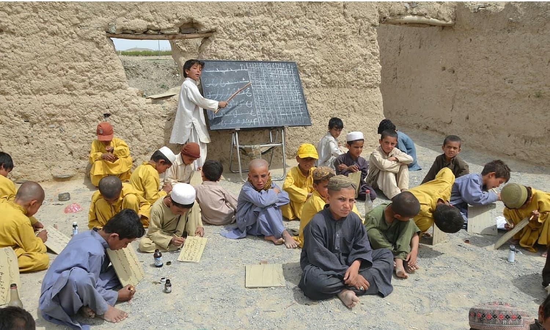 Children sit on the floor at an open-air school in Balochistan. — Asmatullah Khan/File