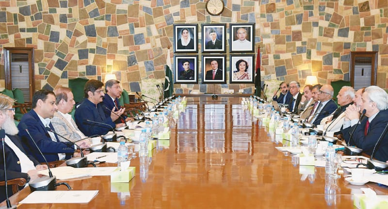 Sindh Chief Minister Syed Murad Ali Shah talks to Petroleum Minister Ghulam Sarwar Khan during a meeting at the CM House in Karachi on Friday.—PPI