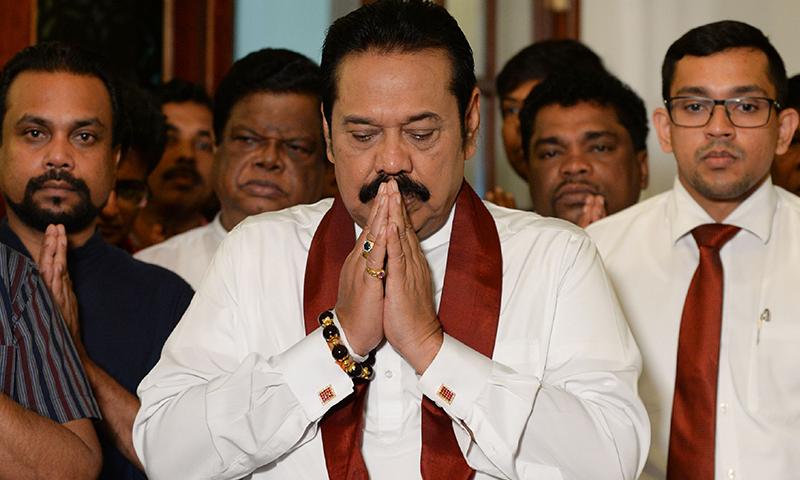 سری لنکا کے وزیرِ اعظم مہندا راجا پکسے کی استعفے پر دستخط کرنے سے قبل لی گئی تصویر — فوٹو، اے ایف پی