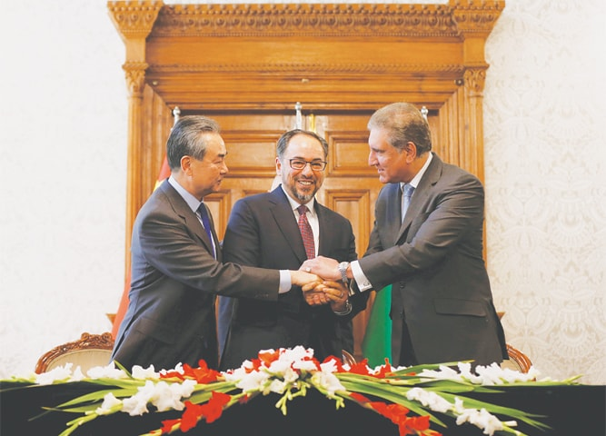 KABUL: Afghan Foreign Minister Salahuddin Rabbani (centre), Foreign Minister Shah Mehmood Qureshi and their Chinese counterpart Wang Yi join hands after a memorandum of understanding on cooperation in fighting terrorism was signed on Saturday.—Reuters