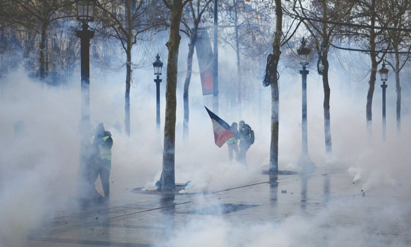 Paris: Demonstrators appear through tear gas during scuffles on the Champs-Elysees avenue on Saturday.—AP