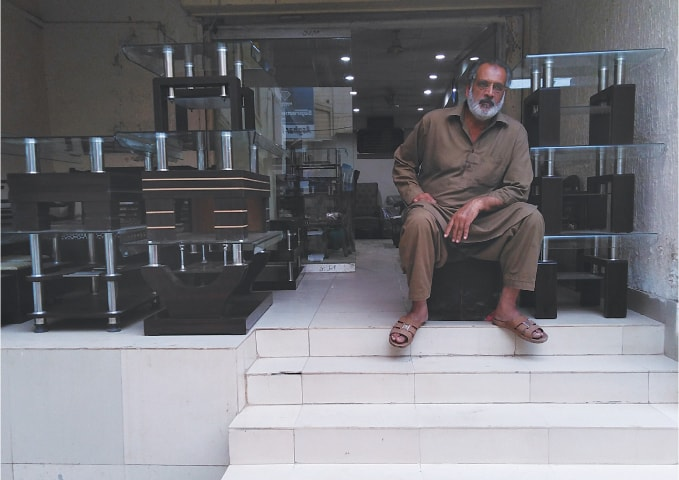 A shopkeeper at the Nursery furniture market in Karachi awaits customers