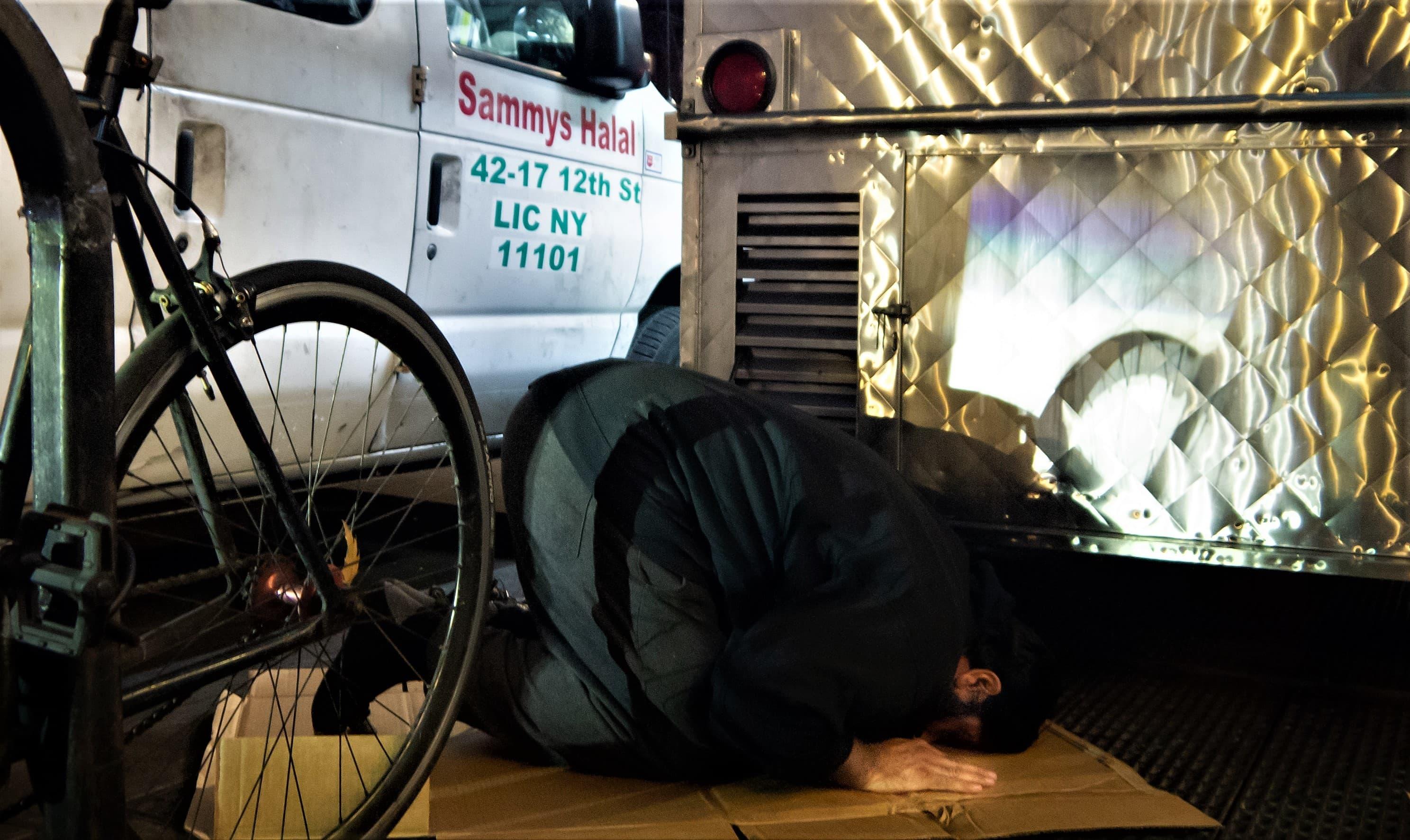 Adnan says Maghrib prayers outside his cart.