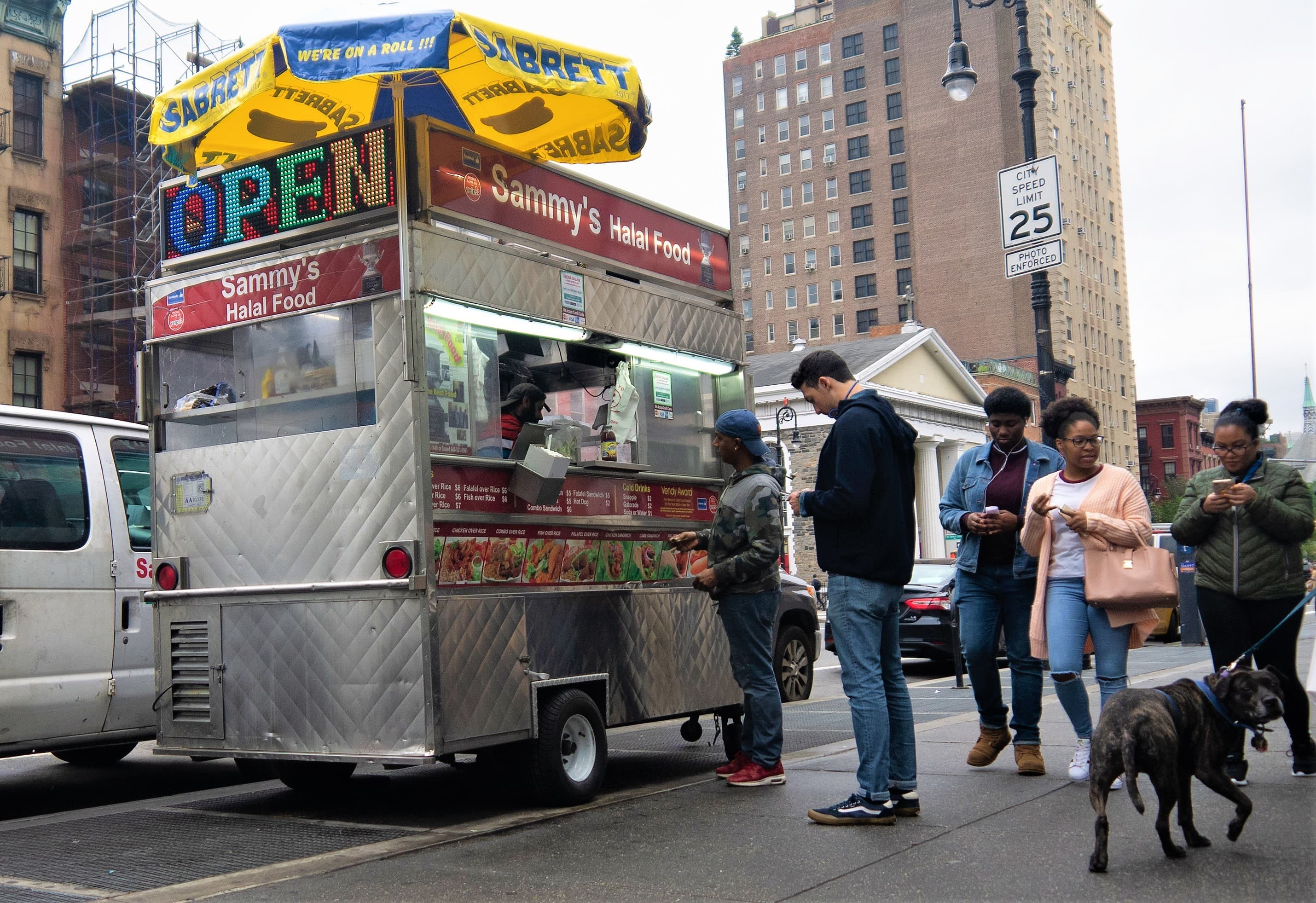 Customers line up outside the cart on the busy 6th Avenue and West 4th Street intersection.