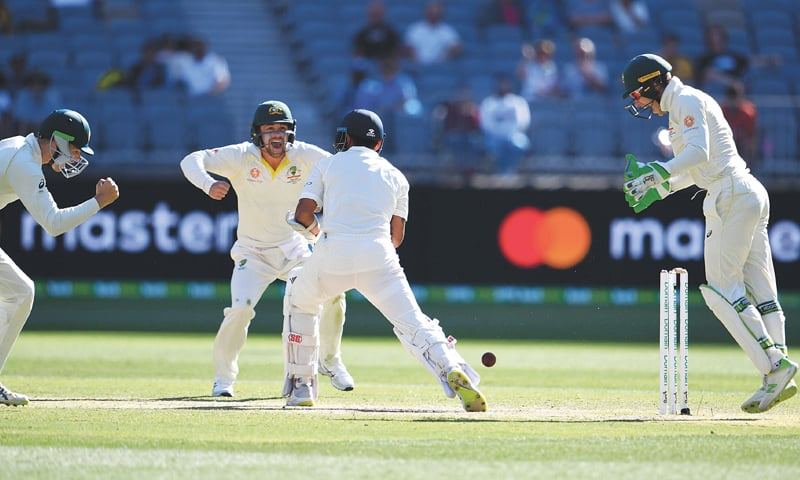 PERTH: Indian opener Murali Vijay is clean bowled by Australian off-spinner Nathan Lyon as wicket-keeper Tim Paine and close-in fielders celebrate during the second Test at Perth Stadium on Monday.—AFP