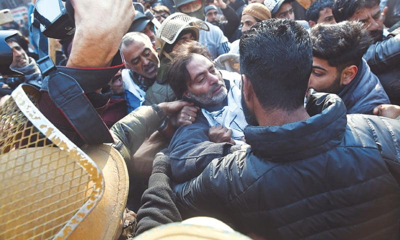 KASHMIRI leader Yasin Malik (centre) and other demonstrators scuffle with Indian police in Srinagar on Monday as they try to march during a protest against the recent killing of civilians in held Kashmir.—AFP