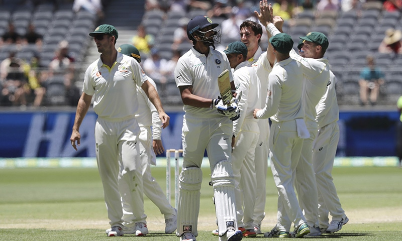 India's Ishant Sharma, center, walks off after being dismissed as Australian player celebrate during play in the second cricket test between Australia and India in Perth. — AP
