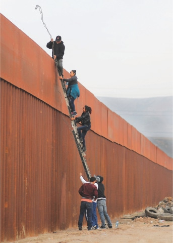 Tijuana (Mexico): Migrants from Honduras, part of a caravan of thousands from Central America trying to reach the United States, climb a border fence to cross illegally from Mexico to the US on Friday.—Reuters