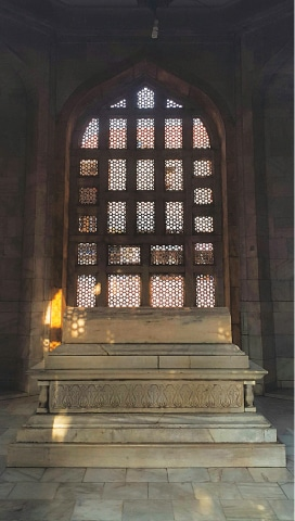 The chamber of Aibak's tomb with a marble structure and a 'Sultanate styled' window' in the background of the grave