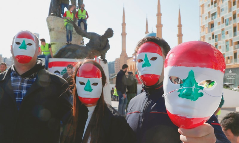 Beirut: Anti-government protesters, some in yellow vests (background), wear Lebanese-flag-painted masks on Sunday.—AFP