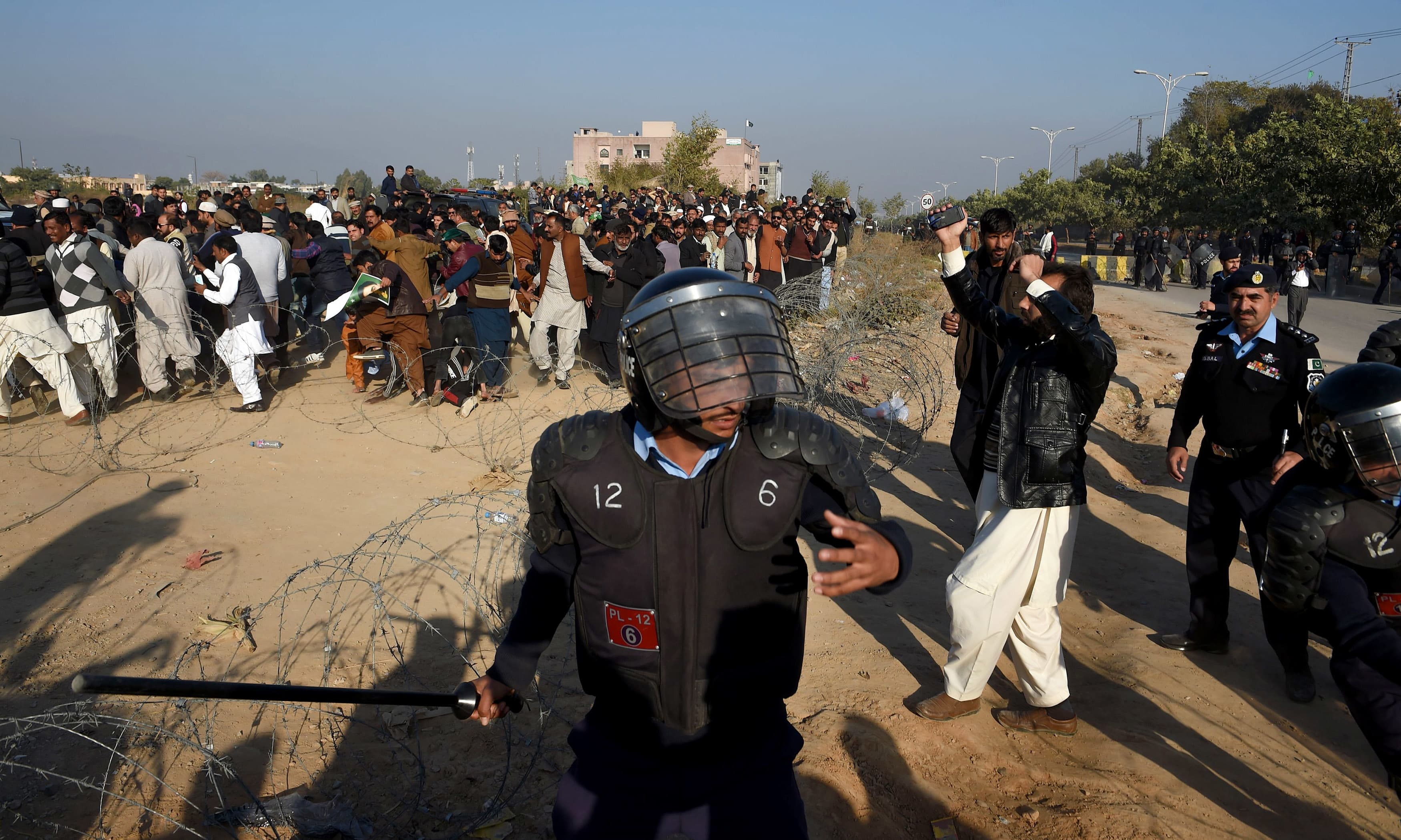 Policemen disperse PML-N supporters outside the anti-corruption court in Islamabad. —AFP