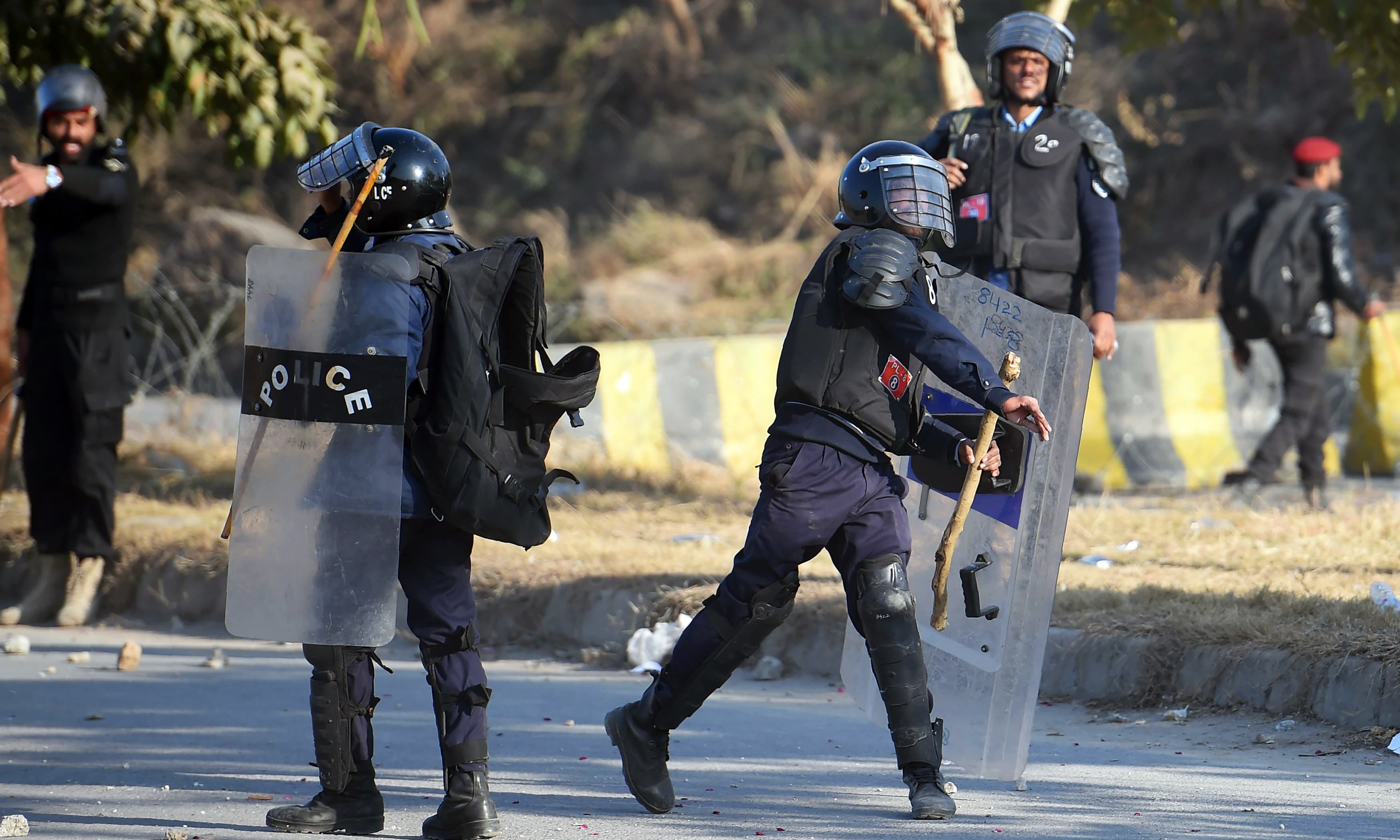 A policeman hurls a stone towards supporters of Nawaz Sharif outside the anti-corruption court in Islamabad. —AFP