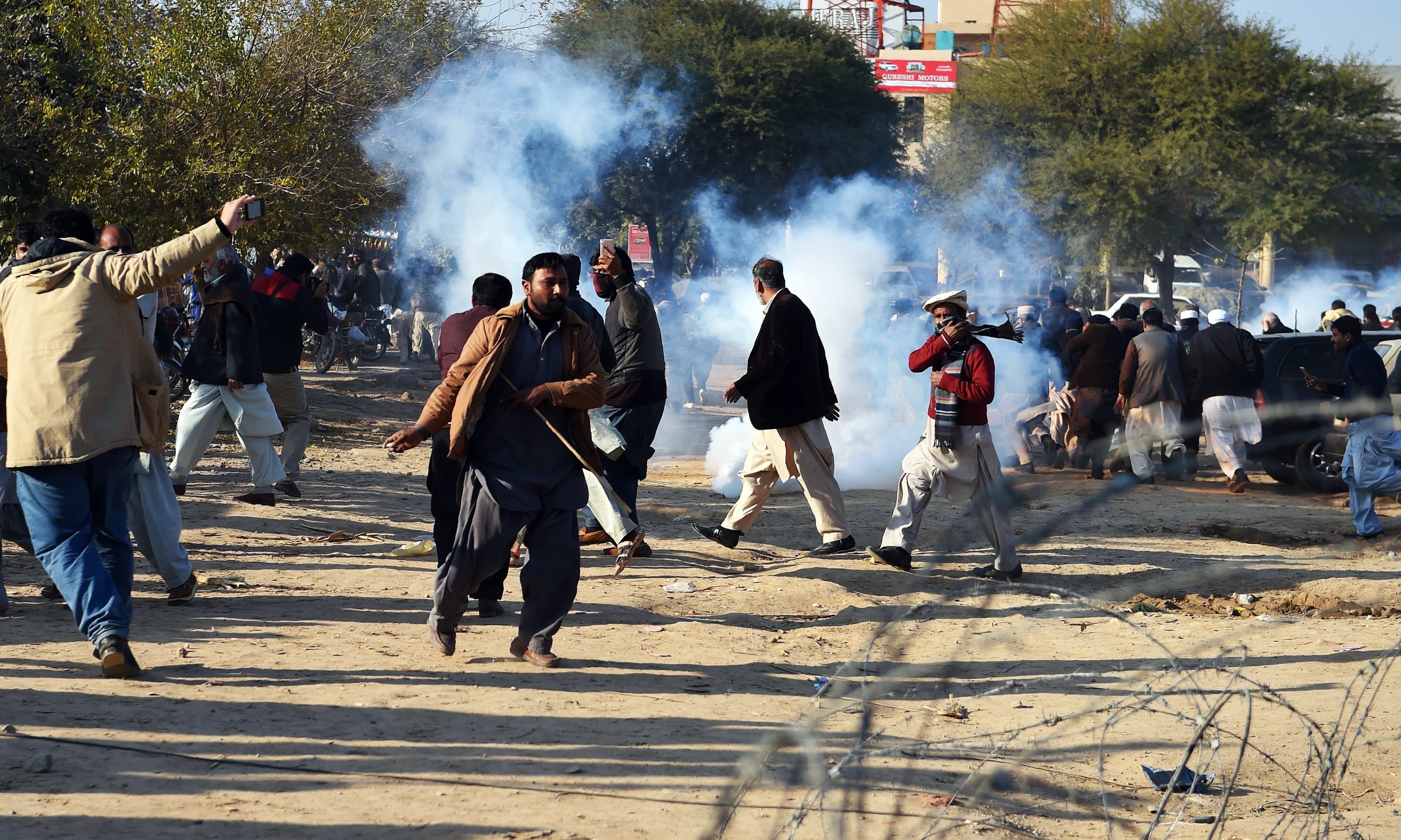 Supporters of Nawaz Sharif run from tear gas shell outside the anti-corruption court in Islamabad. —AFP