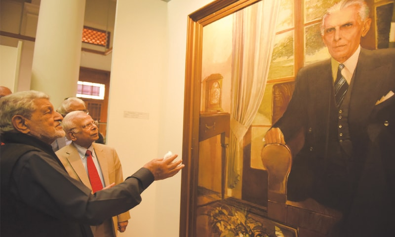 The artist (L) tells chief guest Dr Ishrat Hussain about one of his Quaid portraits borrowed from Sindh Governor House for the exhibition. —Tahir Jamal / White Star