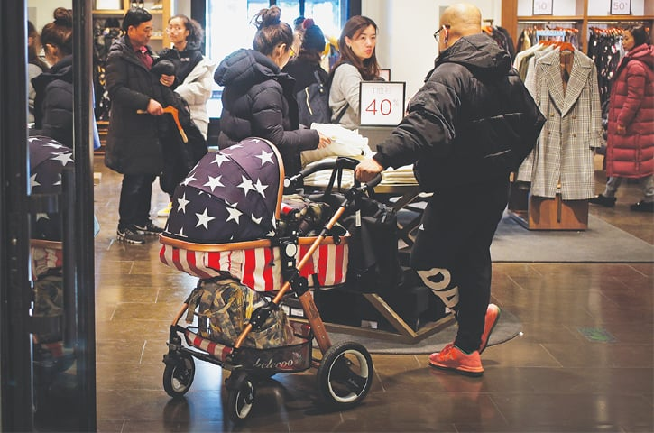 BEIJING: A Chinese man holds a baby stroller with an American flag design as he and his family members visit at a fashion boutique on Tuesday. China's legislature is considering a law to prohibit government officials from pressuring foreign companies to hand over technology, a practice that helped spark Washington's tariff war with Beijing. -AP