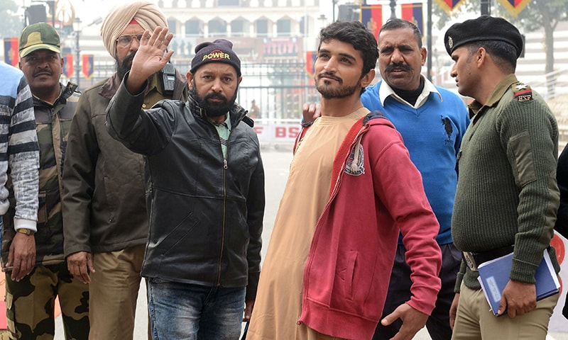 Released Pakistani prisoners Abdullah Shah (3R) and Mohammad Imran Warsi (2L) gesture as they prepare to cross the India-Pakistan border in Wagah on Wednesday. — AFP