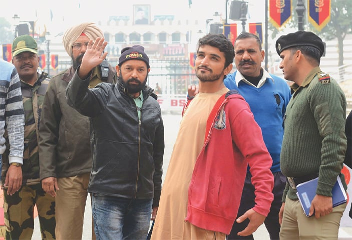 ABDULLAH Shah (third right) and Mohammad Imran Qureshi Warsi gesture as they prepare to cross the India-Pakistan border at Wagah on Wednesday. Indian authorities said the two Pakistanis were granted their freedom as a goodwill gesture.—AFP