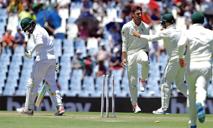 South African paceman Duanne Olivier (C) celebrates with team-mates after dismissing Mohammad Amir (L) during the first Test. —AP