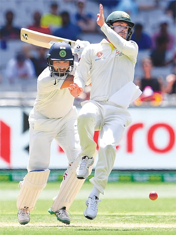 MELBOURNE: Indian batsman Cheteshwar Pujara plays a shot as Australia's Travis Head takes evasive action.—AFP